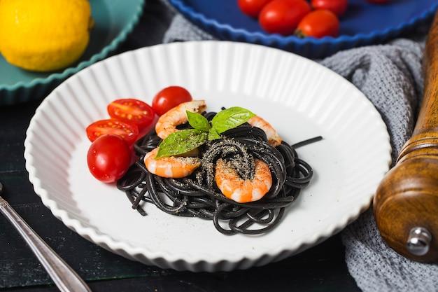 Schwarze spaghetti mit garnelen auf weißer platte