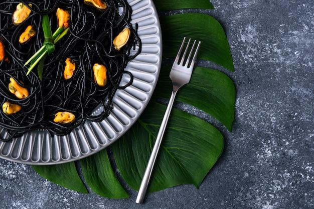 Schwarze spaghetti mit tinten-tintenfisch mit muscheln in grauer platte auf grünem blatt und gabel auf grauem hintergrund, meeresfrüchtekonzept