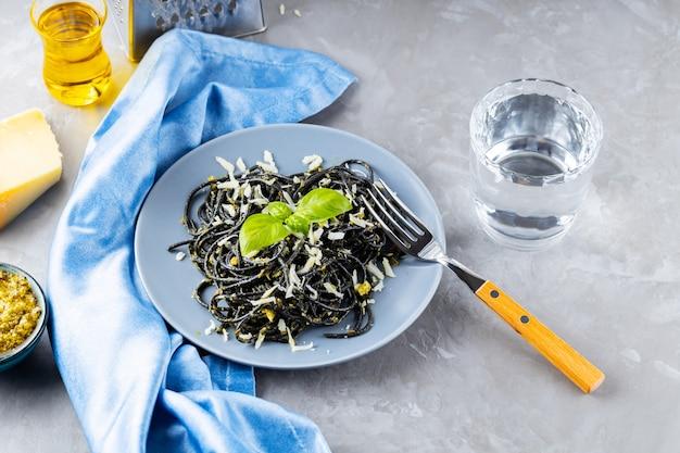Schwarze spaghetti mit tintenfischtinte auf grauem hintergrund. schwarze nudeln mit parmesan, basilikum und pesto-sauce. pasta mit geriebenem käse und zutaten. ansicht von oben