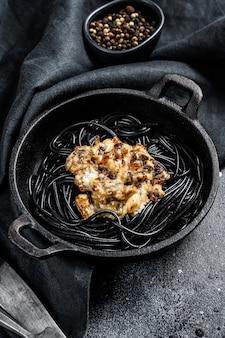 Schwarze spaghetti-nudeln mit lachs in sahnesauce. schwarzer hintergrund. draufsicht