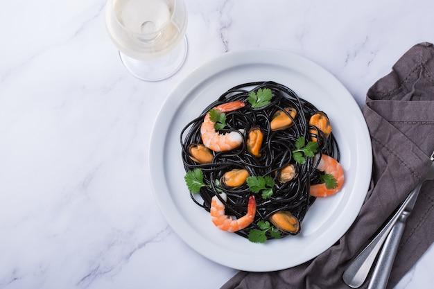 Schwarze spaghetti-nudeln mit meeresfrüchten, garnelen, muscheln und petersilie