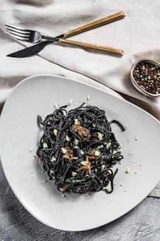 Schwarze spaghetti-nudeln mit rindfleisch in pfeffersauce und parmesan. .