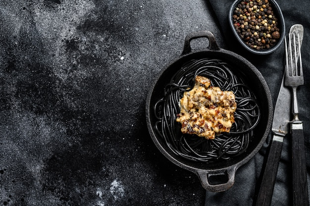 Schwarze spaghetti-nudeln mit tintenfisch in einer pfanne. rindfleisch in pfeffersauce. schwarzer hintergrund. draufsicht. speicherplatz kopieren