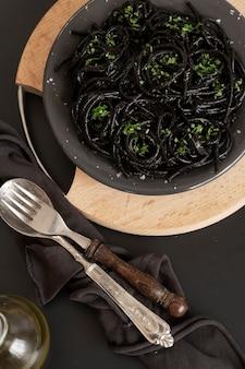 Schwarze spaghetti-nudeln mit tintenfischtinte. schwarze meeresfrüchtenudeln auf dunklem hintergrund. mediterrane delikatesse.