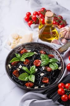 Schwarze spaghetti-nudeln mit tomaten-käse und basilikum