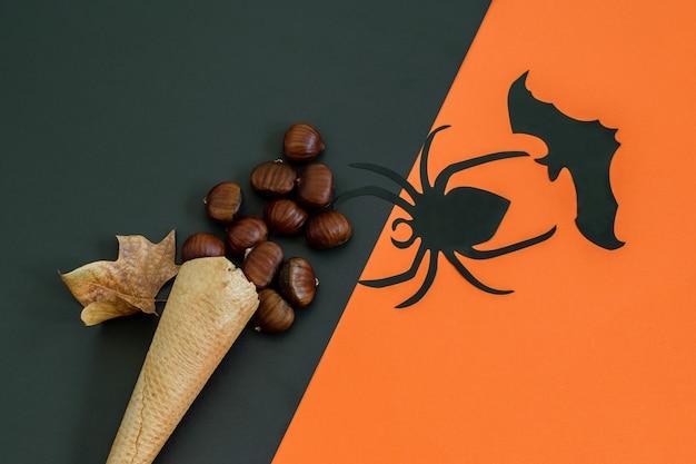 Schwarze spinne, fledermaus und waffeleistüte mit kastanien auf dem schwarz-orangefarbenen papier