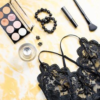 Schwarze spitzenwäsche mit schönheitspflegeprodukten, make-up-kosmetik, schmuck in schwarz und gold. mode flach legen, draufsicht