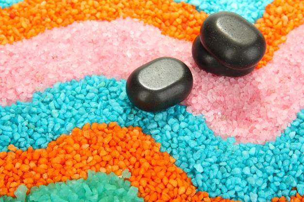 Schwarze steine auf bunten meersalzkristallen