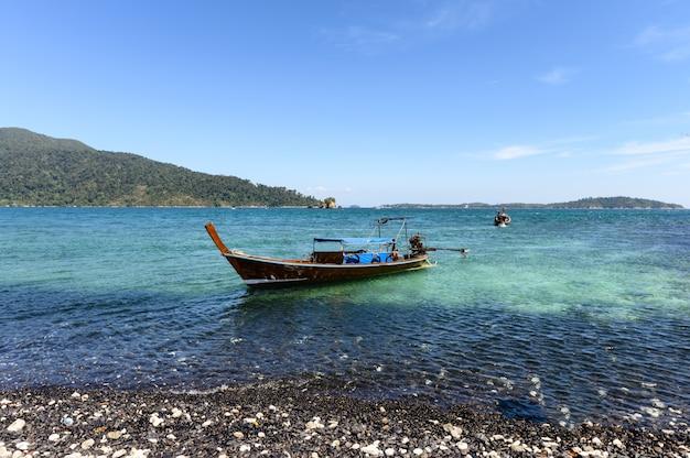 Schwarze steininsel mit hölzernem boot auf küstenlinie im tropischen meer