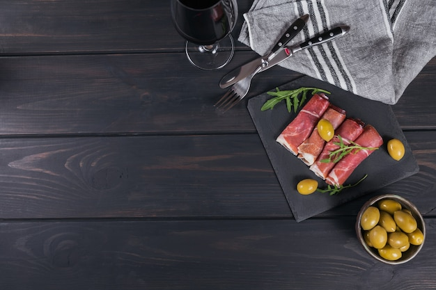 Schwarze steinplatte mit schinkenscheiben oder spanischem jamon serrano oder italienischem prosciutto crudo