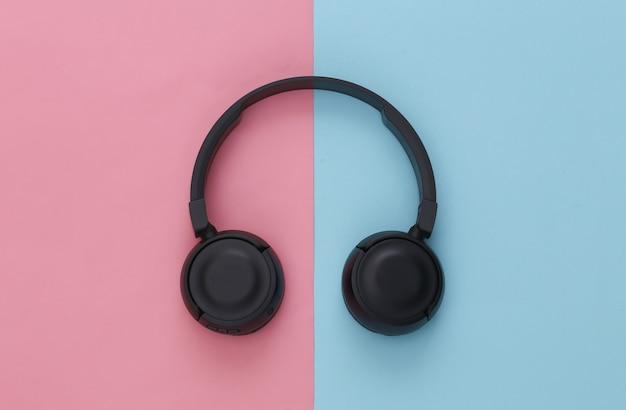 Schwarze stereo-kopfhörer auf rosa blauem pastell
