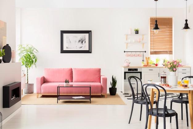 Schwarze stühle am esstisch in weißem, flachem interieur mit küchenzeile und poster über der couch. echtes foto