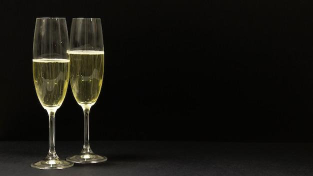 Schwarze szene mit zwei gläsern champagner.