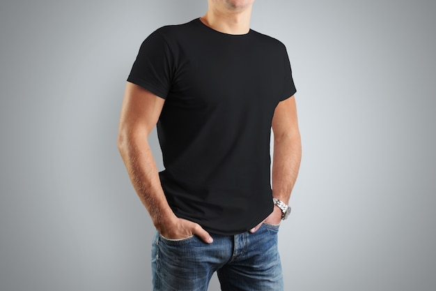 Schwarze t-shirts. ein junger athletischer mann ist auf einer grauen wand isoliert.