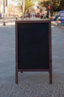 Schwarze tafel auf der straße annoncieren. platz für text, poster oder öffentliche informationen.