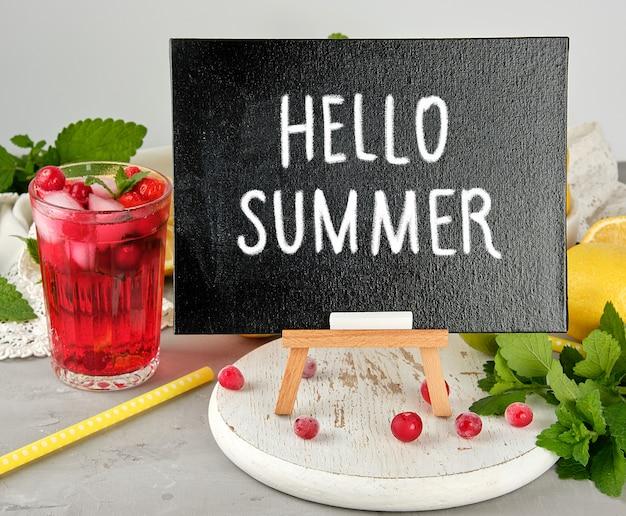 Schwarze tafel zum schreiben eines sommergetränkerezepts und eines glases mit beerenlimonade