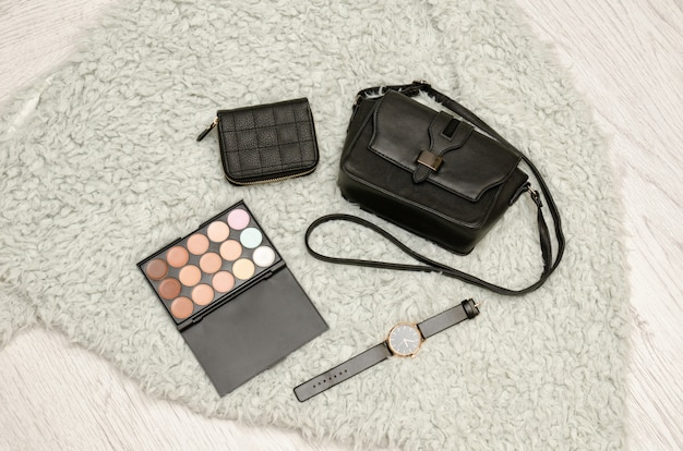 Schwarze tasche, lidschatten, uhr, geldbörse. graues fell auf hintergrund, draufsicht. modekonzept