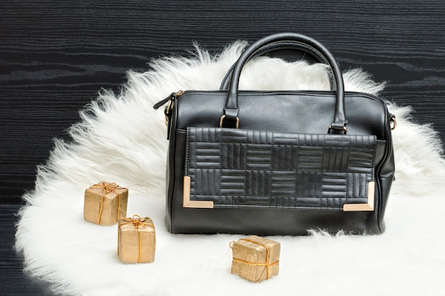 Schwarze tasche und geschenkbox auf weißem pelz feiertagseinkaufen