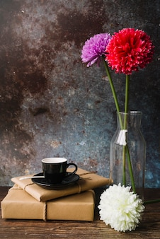 Schwarze tasse und untertasse auf eingewickelten geschenkboxen aus braunem papier mit schönen blumen