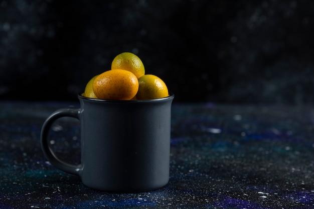Schwarze tasse voll mit bio-kumquats