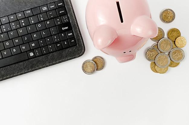 Schwarze tastatur und sparbüchse mit euro-münzen an der weißen wand. geld sparen konzept. draufsicht, kopierraum.