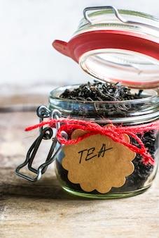 Schwarze teeblätter auf rustikalem