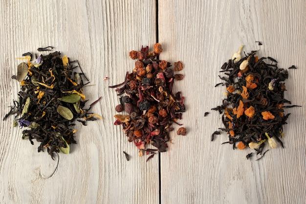 Schwarze teeblätter mit getrockneten früchten und blumen