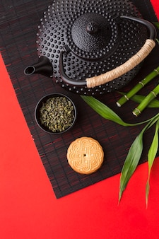 Schwarze teekanne der draufsicht mit keksen