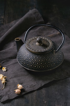 Schwarze teekanne mit trockenen rosen