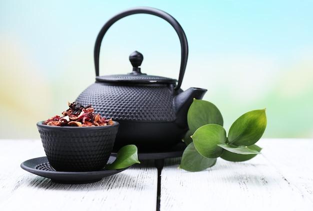 Schwarze teekanne, schüssel und tee auf farbigem holztisch, auf hellem hintergrund