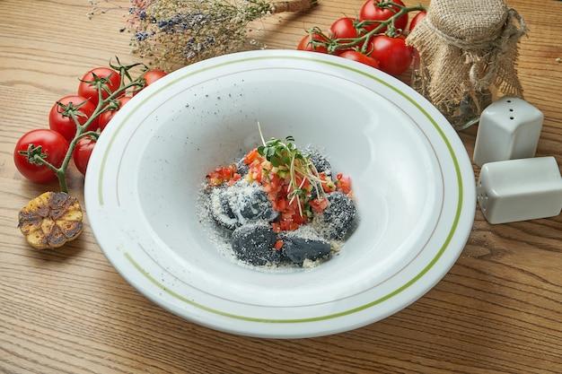 Schwarze teigknödel mit füllung und tomatensalsa in einem weißen teller auf einem holztisch. schwarze italienische ravioli mit garnelen und hühnchen
