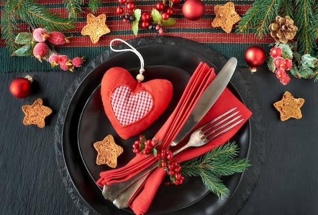 Schwarze teller und weinlesebesteck mit weihnachtsdekorationen auf schwarzem stein