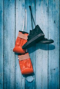 Schwarze textilschuhe und rote boxhandschuhe aus leder