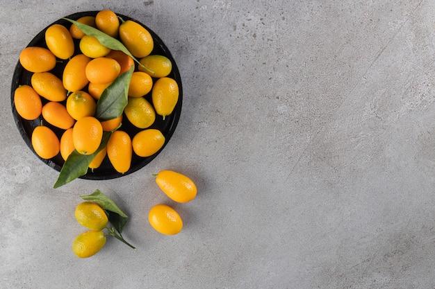 Schwarze tiefe schüssel mit frischen saftigen kumquats auf steinoberfläche