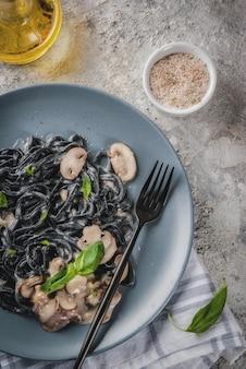Schwarze tintenfisch-tintenspaghettiteigwaren des modernen italienischen abendessens mittelmeerlebensmittels mit olivenöl und basilikum der champignonpilze