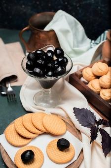 Schwarze traditionelle walnusskonfektion in einem glas mit butterkeksen herum
