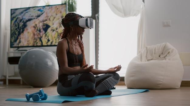 Schwarze trainerin, die ein virtual-reality-headset trägt, während sie auf einer yoga-karte sitzt