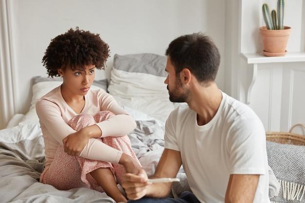Schwarze traurige frau zeigt ihrem partner ein positives ergebnis beim schwangerschaftstest