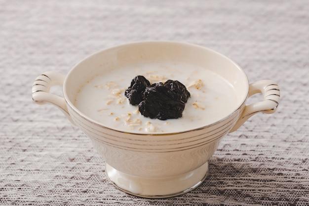 Schwarze trockene pflaumen auf dem hafermehlfrühstück über dem tischset