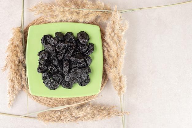 Schwarze trockene pflaumen in einer keramikplatte auf beton.
