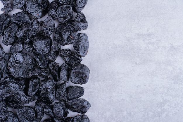 Schwarze trockene pflaumen isoliert auf betonoberfläche