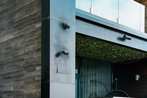 Schwarze überwachungskameras auf dem gesicht eines schwarzen gebäudes mit schönen balkonen installiert. garten an der decke. horizontale latten aus holz. architekturdesign. überwachungskamera. privatsphäre. sicherheit. spion