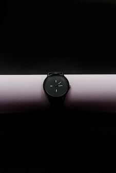 Schwarze uhren auf hellem rohr. abstrakter hintergrund des dunklen schwarzen, ein gegenstand. horizontal
