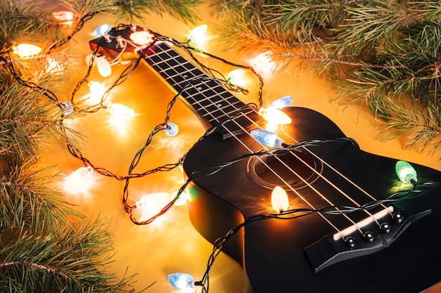 Schwarze ukulele-gitarre und weihnachtsschmuck auf dunklem hintergrund. hawaiianische gitarre mit beleuchteter girlande auf dunklem hintergrund. klassische formen der geschenkgitarre für weihnachten, neues jahr.