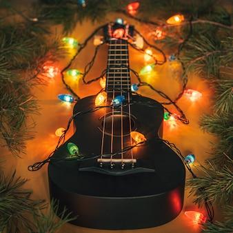 Schwarze ukulele-gitarre und weihnachtsschmuck auf dunklem hintergrund. hawaiianische gitarre mit beleuchteter girlande auf dunklem hintergrund. neujahr und weihnachtsmusik, konzept