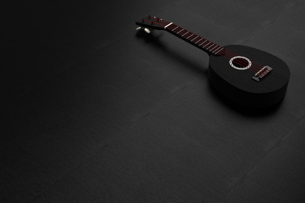 Schwarze ukulelegitarre und rote schnüre auf einem schwarzen hintergrund