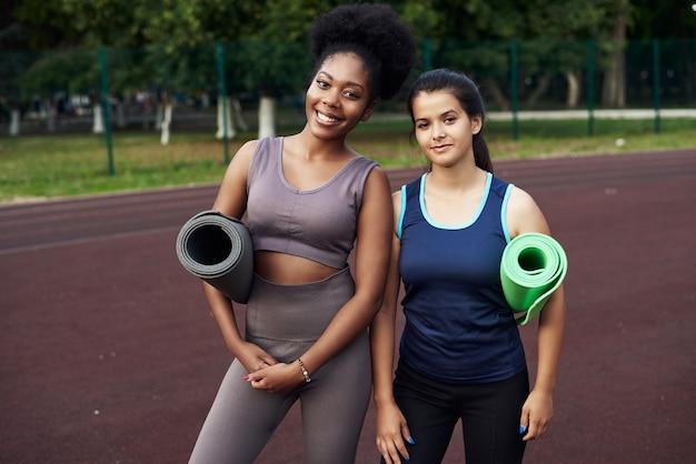 Schwarze und afghanische junge mädchen stehen mit sportmatten in der hand