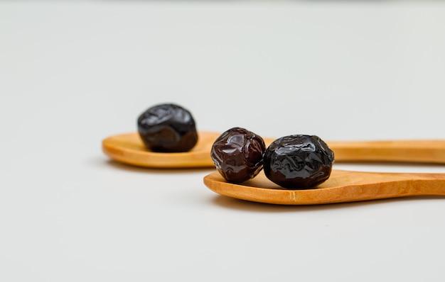 Schwarze und braune oliven in holzlöffeln auf weiß. seitenansicht.