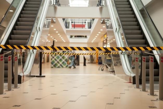 Schwarze und gelbe linien aus absperrband verbieten den zugang zum supermarkt