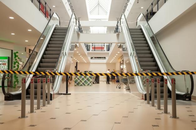 Schwarze und gelbe linien aus absperrband verbieten den zugang zum supermarkt.